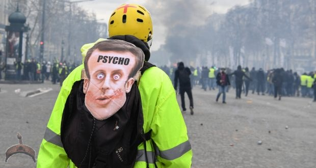 "A Yellow Vest protester wearing a mask depicting the French President on which is written the word 'psycho' looks at fellow protesters in Paris on March 16, 2019, during the 18th consecutive Saturday of demonstrations called by the 'Yellow Vest' (gilets jaunes) movement. - Demonstrators hit French city streets again on March 16, for a 18th consecutive week of nationwide protest against the French President's policies and his top-down style of governing, high cost of living, government tax reforms and for more ""social and economic justice."" (Photo by Alain JOCARD / AFP)"